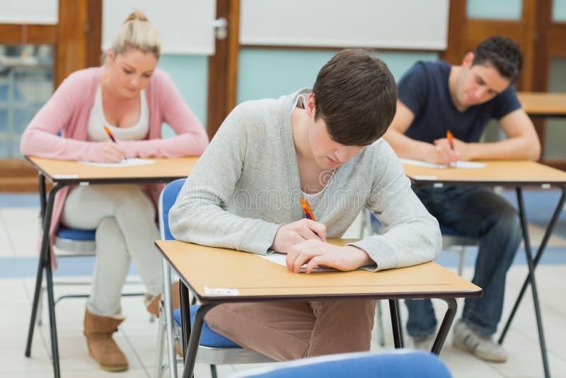 Estudiantes de la escritura en los escritorios en una sala de clase foto de archivo libre de regalías