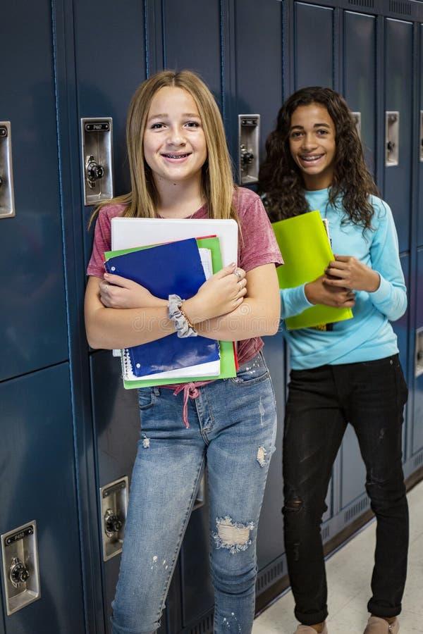 Estudiantes de la escuela de secundaria que hablan y que hacen una pausa su armario en un vest?bulo de la escuela fotos de archivo