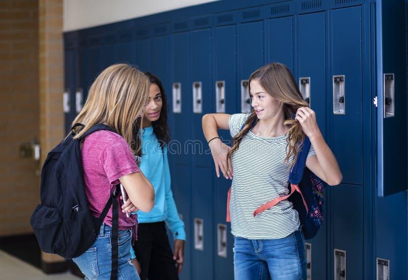 Estudiantes de la escuela de secundaria que hablan y que hacen una pausa su armario en un vest?bulo de la escuela fotografía de archivo libre de regalías