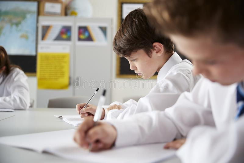 Estudiantes de la escuela secundaria que llevan la sentada uniforme y que trabajan alrededor de la tabla en la lección fotos de archivo libres de regalías