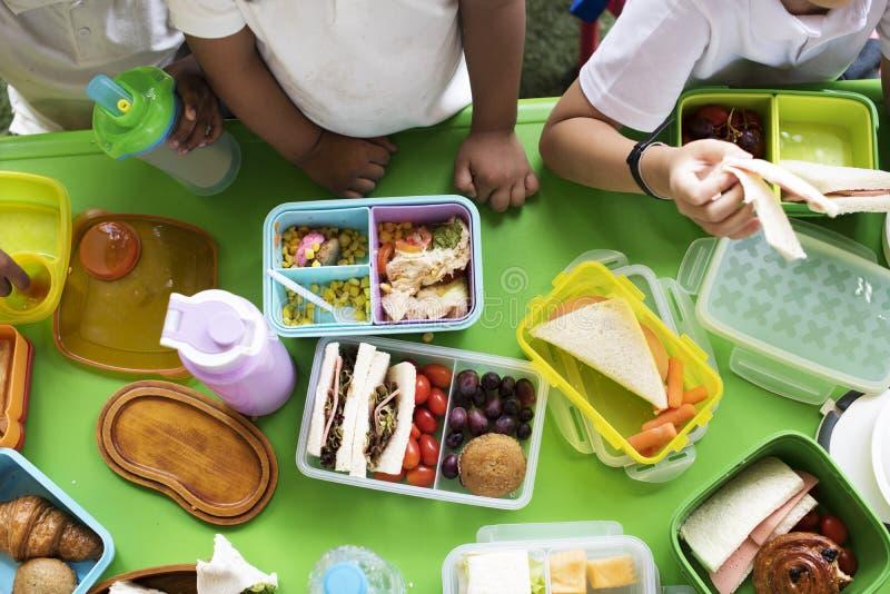 Estudiantes de la guardería que comen la hora de la almuerzo de la comida junto imagenes de archivo