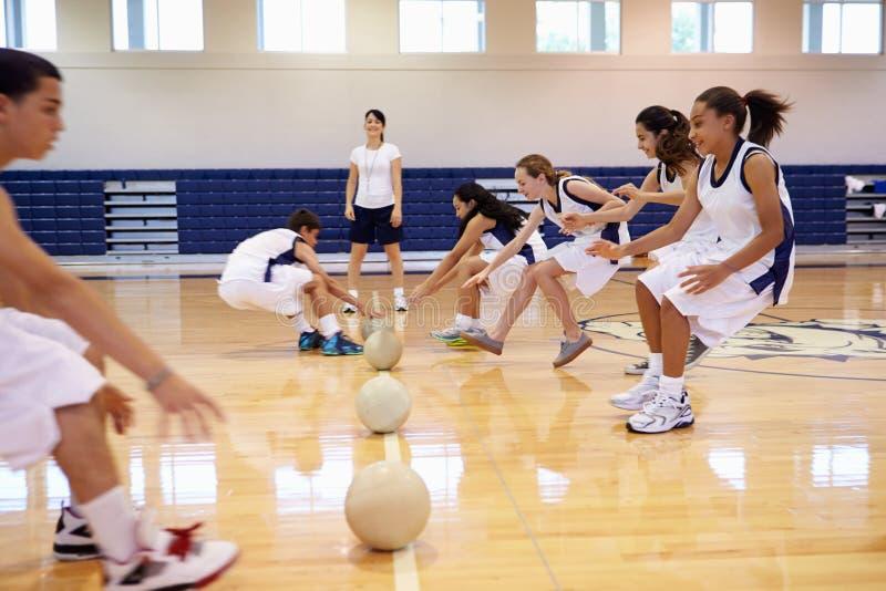 Estudiantes de la High School secundaria que juegan la bola de Dodge en gimnasio imágenes de archivo libres de regalías