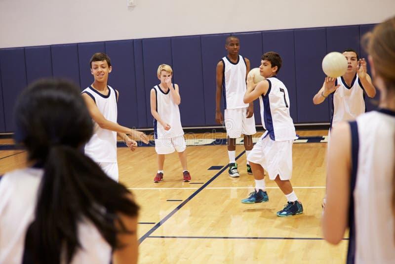 Estudiantes de la High School secundaria que juegan la bola de Dodge en gimnasio fotografía de archivo