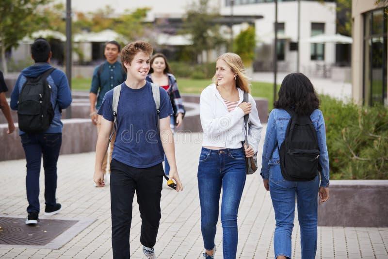 Estudiantes de la High School secundaria que socializan edificios exteriores de la universidad imagen de archivo libre de regalías