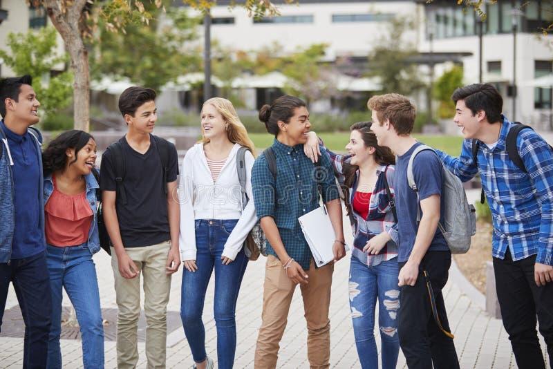 Estudiantes de la High School secundaria que socializan edificios exteriores de la universidad foto de archivo
