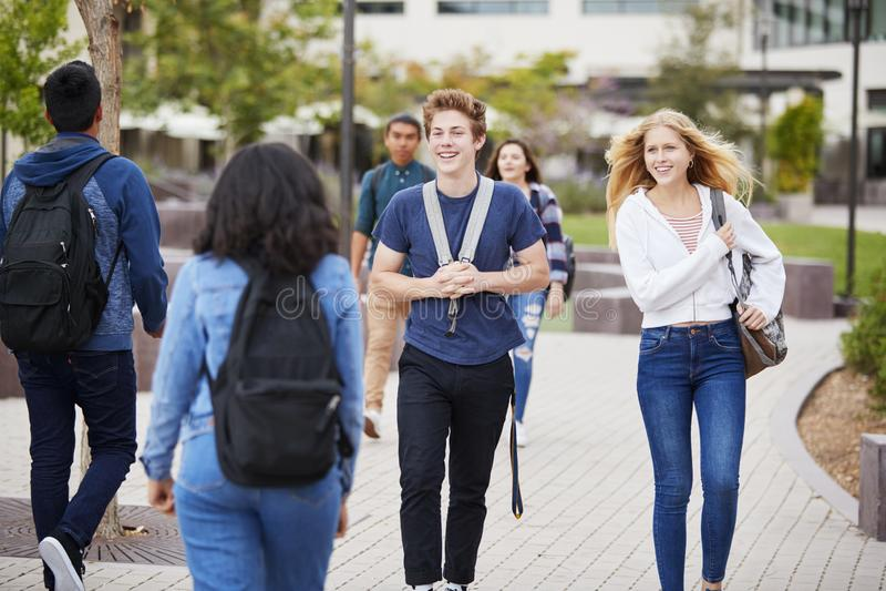 Estudiantes de la High School secundaria que socializan edificios exteriores de la universidad foto de archivo libre de regalías