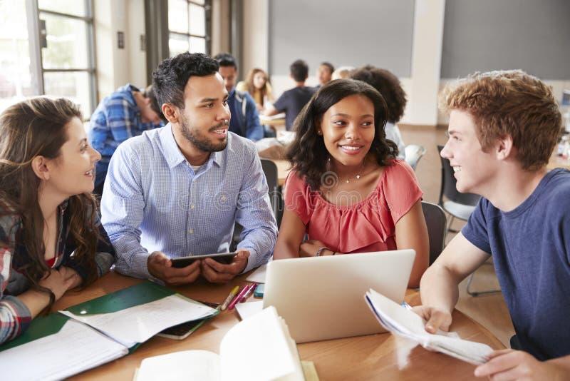 Estudiantes de la High School secundaria que usan los ordenadores portátiles y las tabletas de Digitaces que trabajan con el prof fotos de archivo libres de regalías