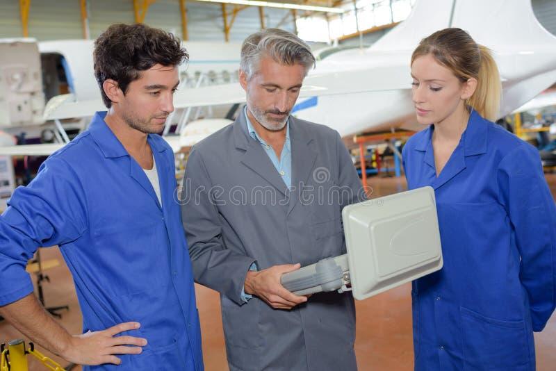 Estudiantes de la ingeniería que miran el equipo de aviones imagen de archivo