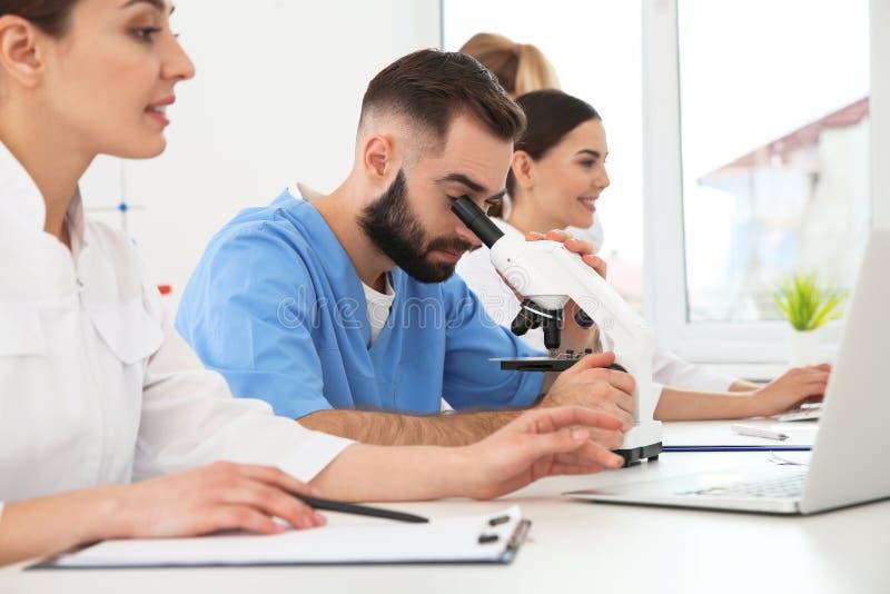 Estudiantes de medicina que trabajan en laboratorio cient?fico foto de archivo