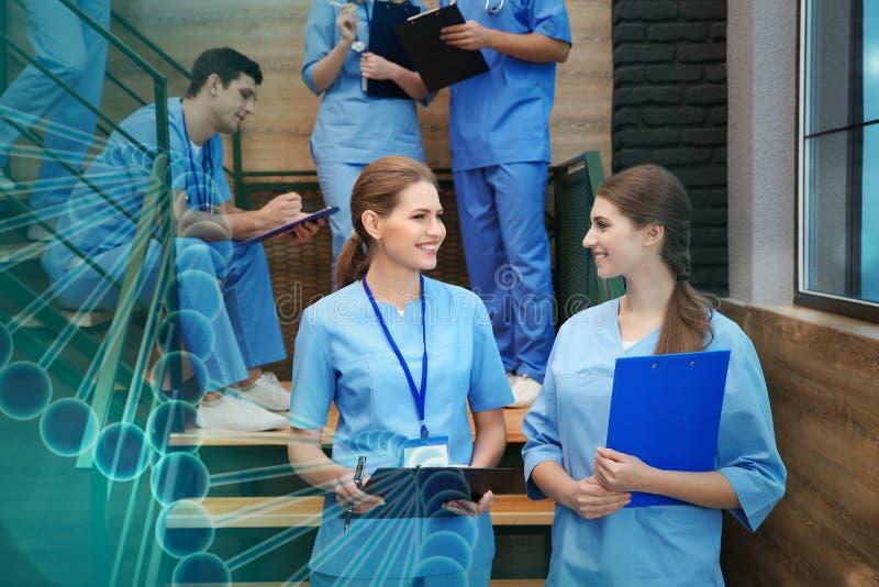 Estudiantes de medicina sonrientes en pasillo de la universidad foto de archivo
