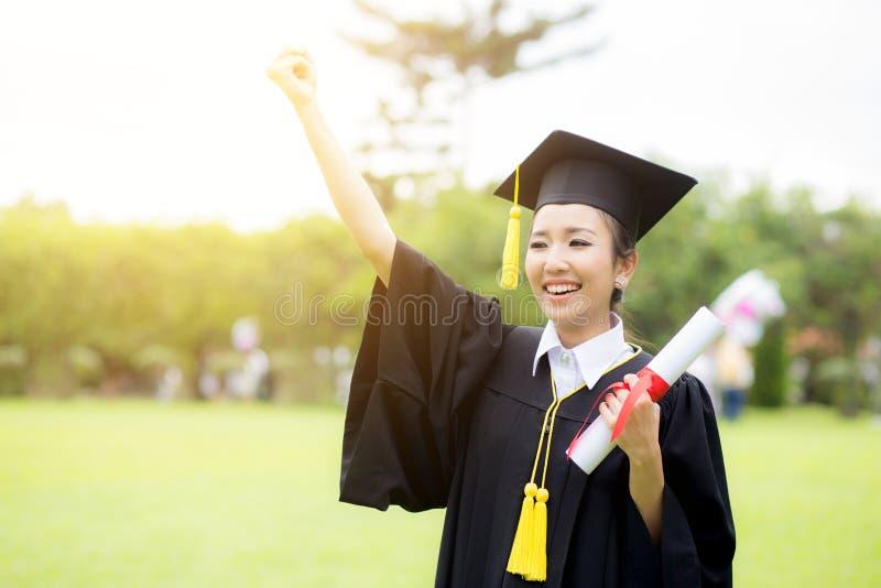 Estudiantes de mujer graduados que llevan el sombrero y el vestido de la graduación imagenes de archivo
