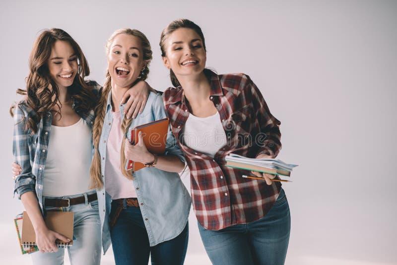 Estudiantes de mujeres felices jovenes con los libros de texto en manos imágenes de archivo libres de regalías