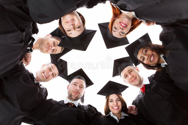 Estudiantes de tercer ciclo que se colocan en el círculo que se inclina hacia cámara imagen de archivo
