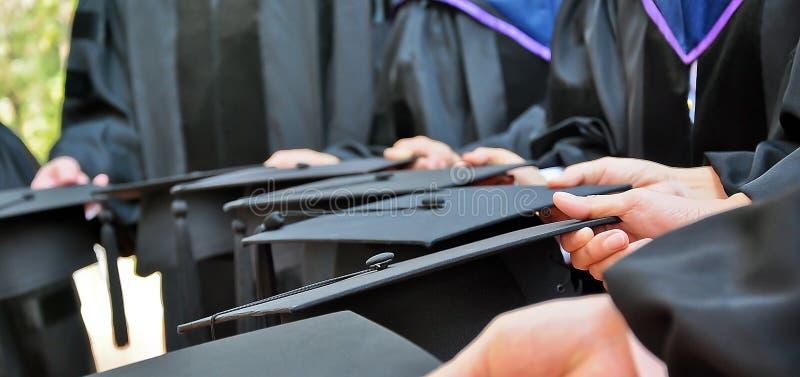 Estudiantes de tercer ciclo que sostienen los sombreros imagen de archivo