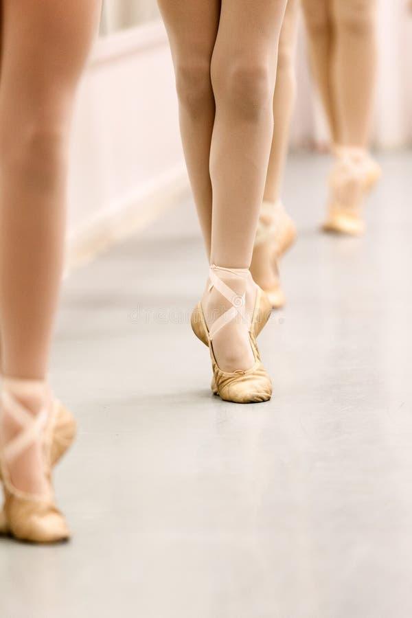 Estudiantes del ballet del adolescente de Pre-Pointe que practican el trabajo de la barra para las posiciones de los pies del bal foto de archivo libre de regalías