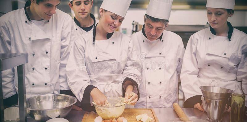 A estudiantes del chef de repostería mostrando cómo preparar la pasta imagen de archivo libre de regalías