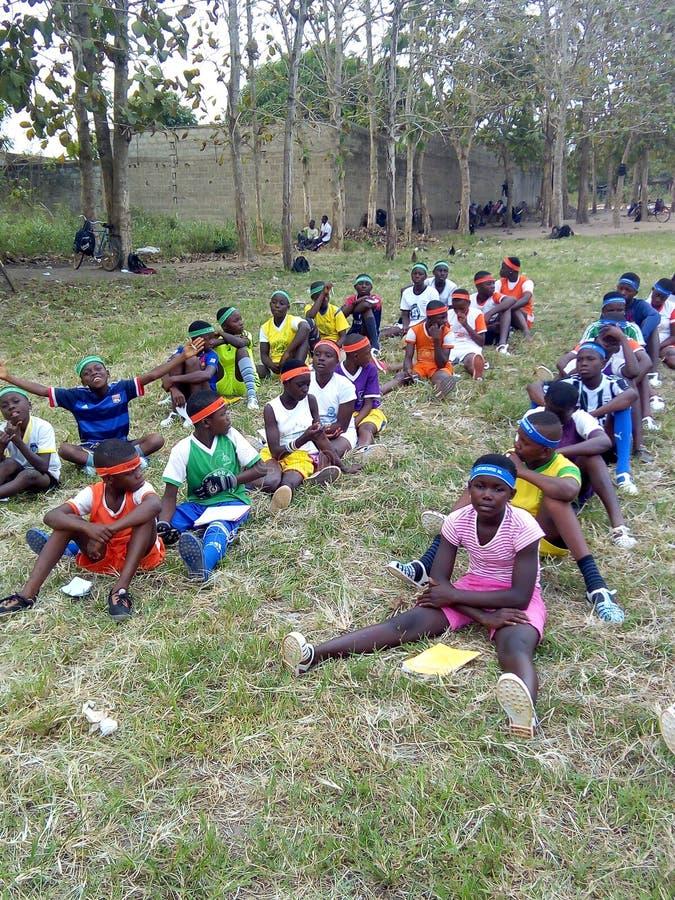 Estudiantes del deporte que se sientan en la hierba para la clase del deporte fotografía de archivo