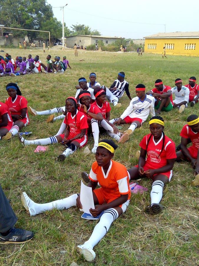 Estudiantes del deporte que se sientan en la hierba para la clase del deporte foto de archivo