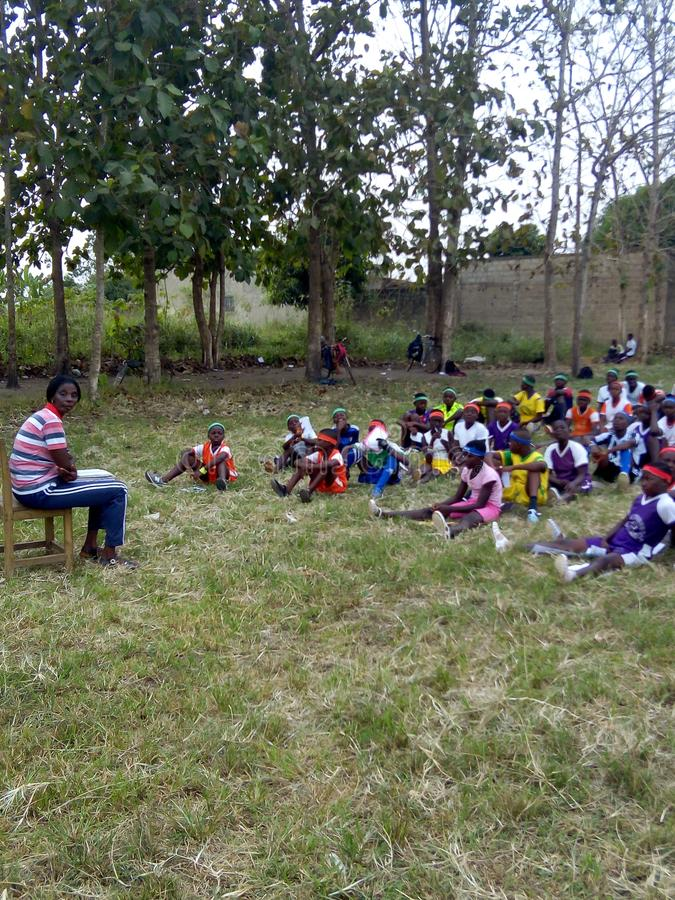 Estudiantes del deporte que se sientan en la hierba para la clase del deporte imagenes de archivo