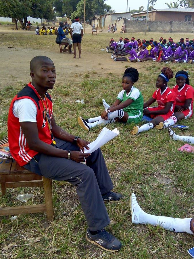 Estudiantes del deporte que se sientan en la hierba para la clase del deporte foto de archivo libre de regalías