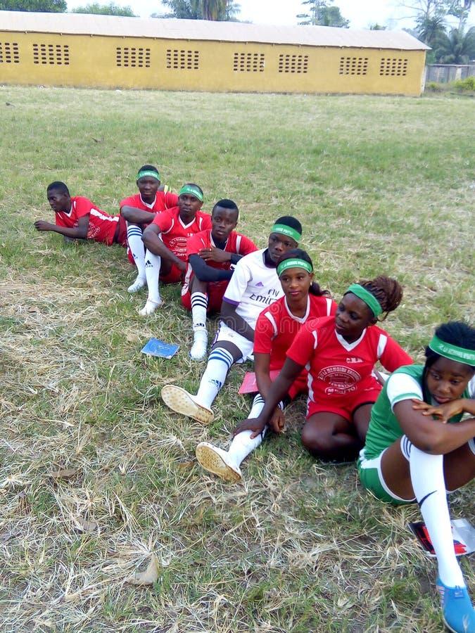Estudiantes del deporte que se sientan en la hierba para la clase del deporte imagen de archivo libre de regalías