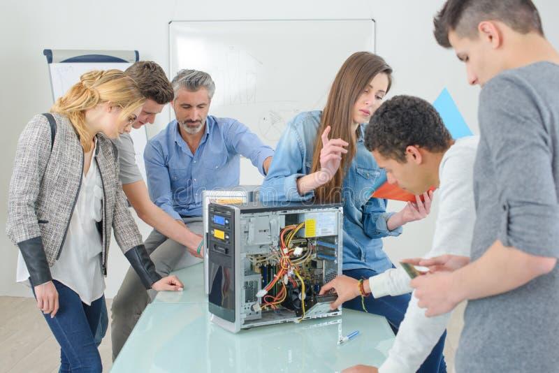 Estudiantes del grupo que fijan el ordenador durante él clase foto de archivo libre de regalías