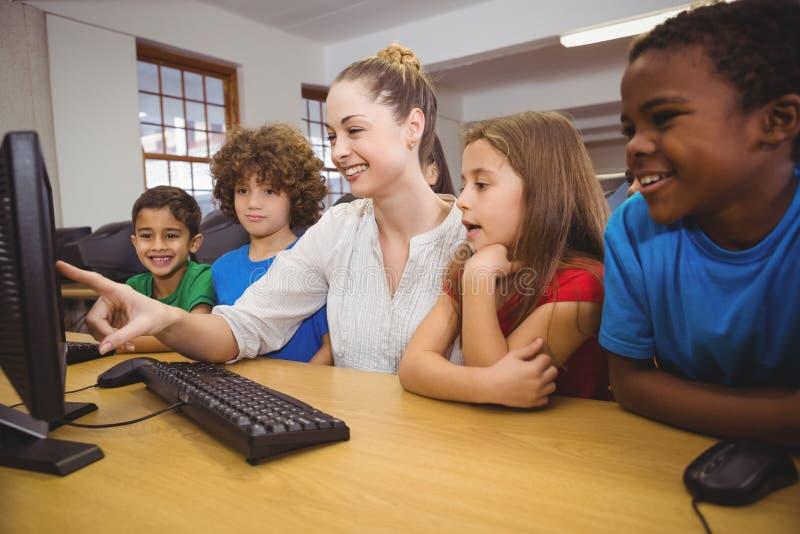 A estudiantes del profesor mostrando cómo utilizar un ordenador imagen de archivo