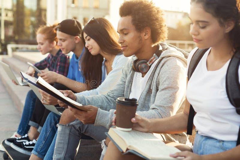 Estudiantes diversos adolescentes que estudian al aire libre por la tarde foto de archivo libre de regalías