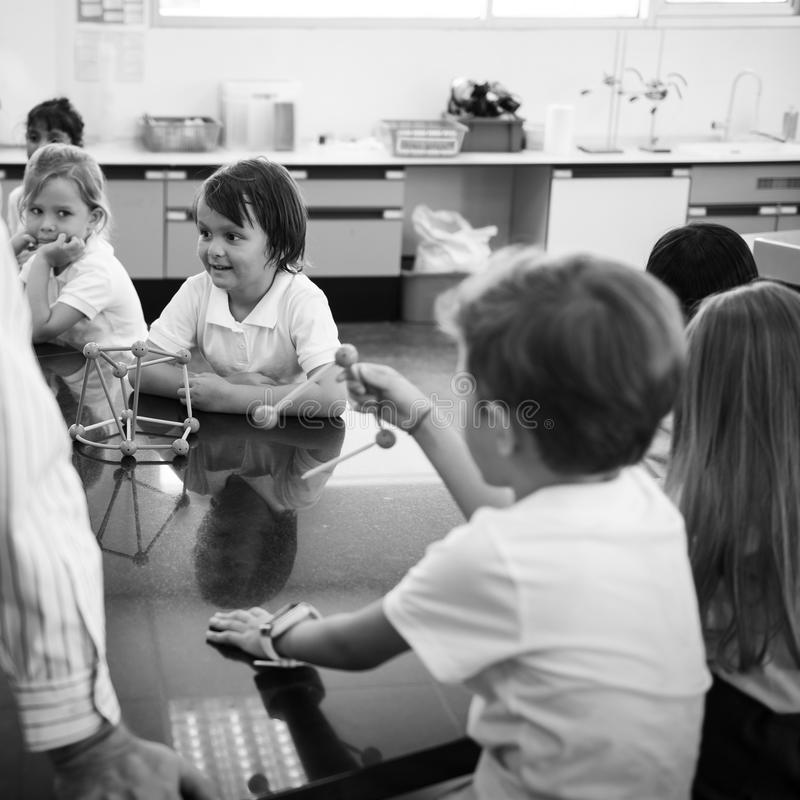 Estudiantes diversos de la guardería que celebran el aprendizaje de la forma de las estructuras fotografía de archivo