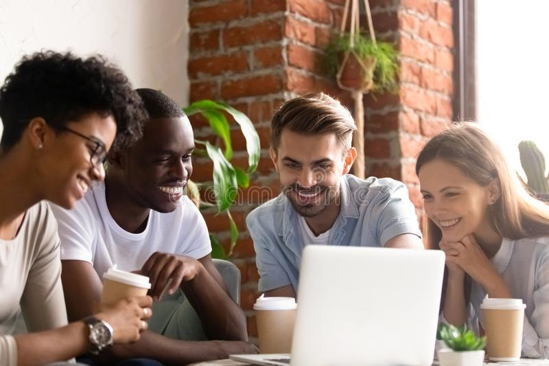 Estudiantes divertidos que miran película en Internet en cafetería foto de archivo
