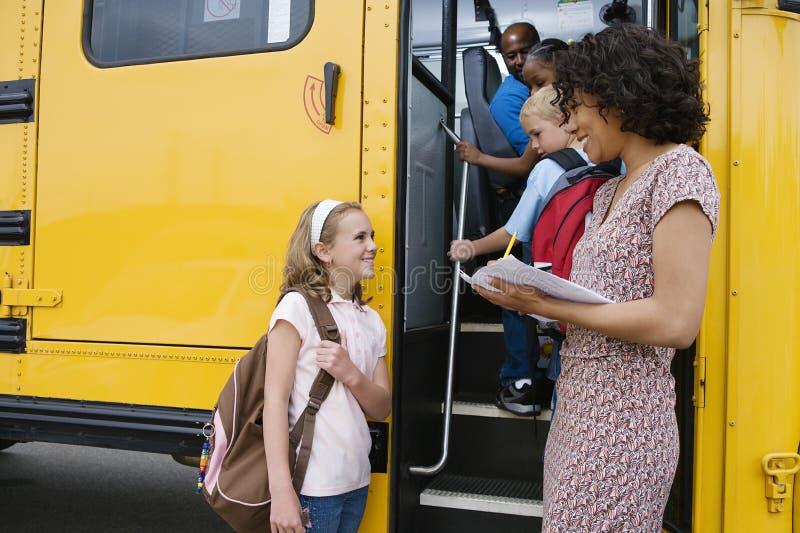 Estudiantes elementales que suben al autobús escolar imágenes de archivo libres de regalías