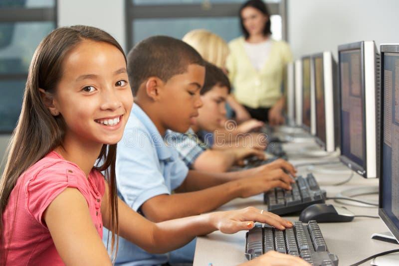 Estudiantes elementales que trabajan en los ordenadores en sala de clase imagenes de archivo