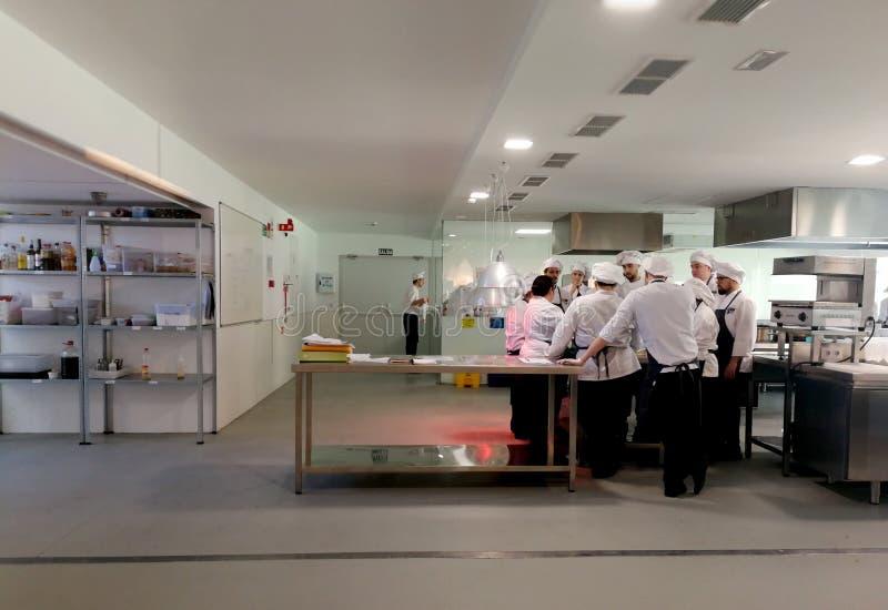 Estudiantes en el funcionamiento de cocinar de la escuela fotos de archivo