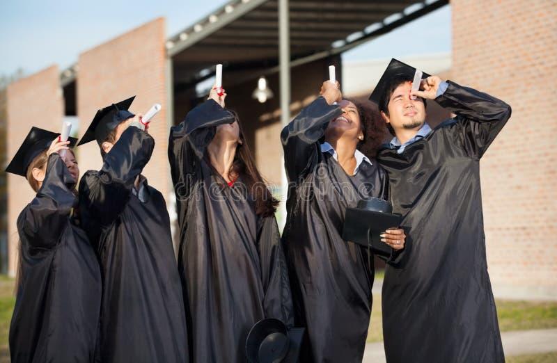 Estudiantes en el vestido de la graduación que mira a través fotografía de archivo