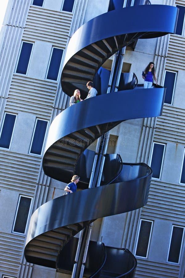 Estudiantes en escalera espiral de la universidad foto de archivo libre de regalías