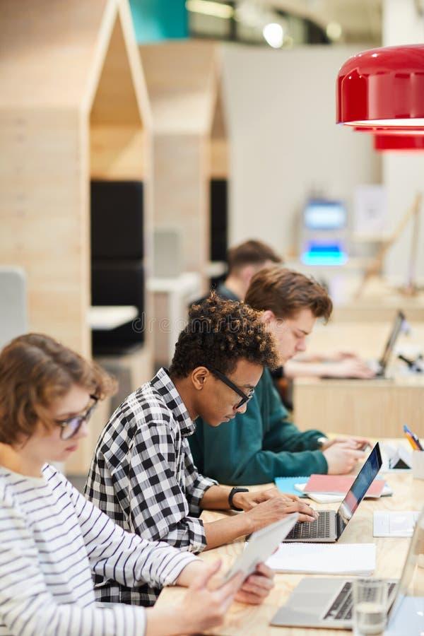 Estudiantes en la línea que hace el hometask en biblioteca imagenes de archivo