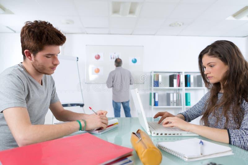 Estudiantes en la lección de la informática y de la programación imagen de archivo libre de regalías