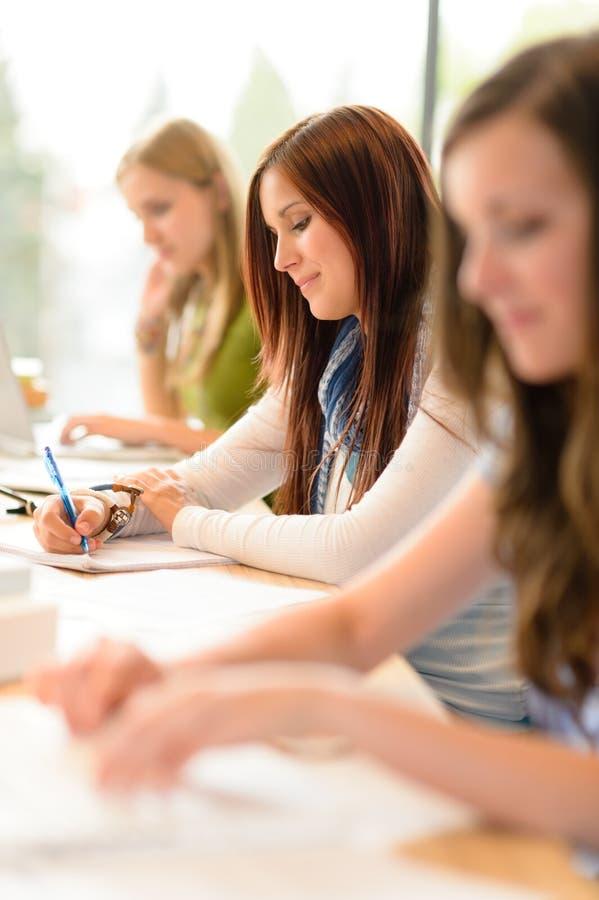 Estudiantes en la sala de clase que se sienta en una fila fotografía de archivo