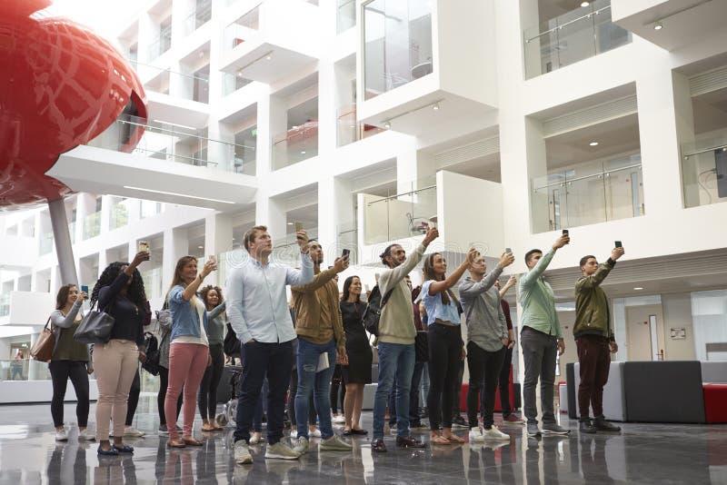 Estudiantes en un atrio de la universidad que toma las fotos con los teléfonos imagen de archivo