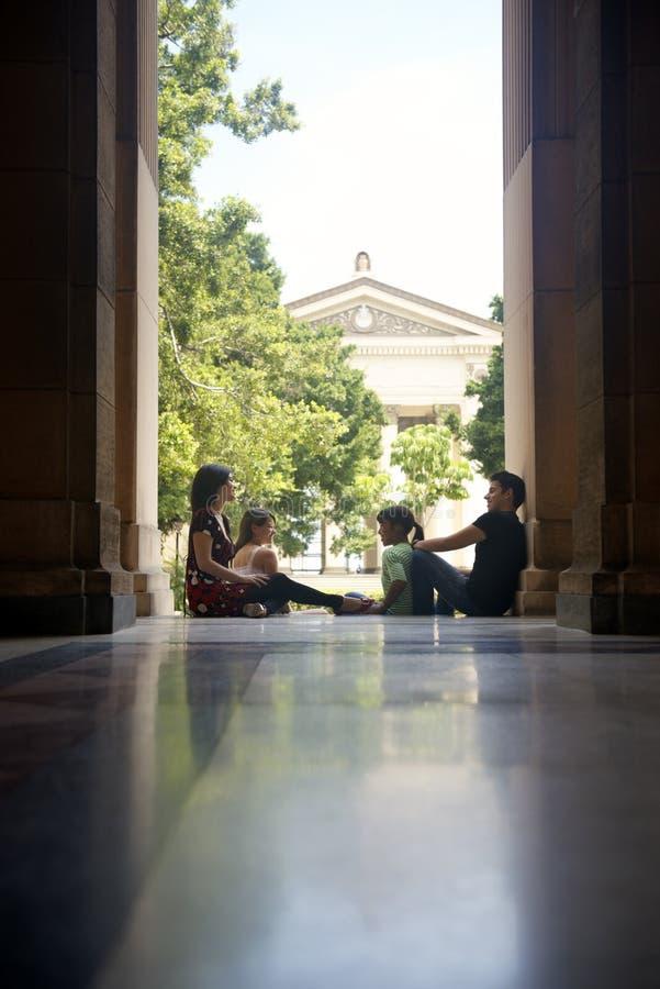 Estudiantes en universidad, grupo de hombres jovenes y el hablar de las mujeres fotos de archivo libres de regalías