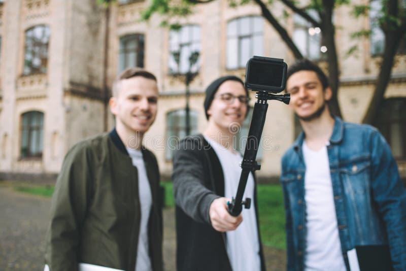 Estudiantes felices acertados que colocan el campus o la universidad cercano afuera imagenes de archivo