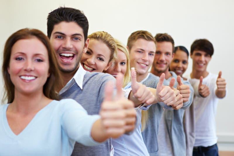 Estudiantes felices con sus pulgares para arriba fotos de archivo libres de regalías