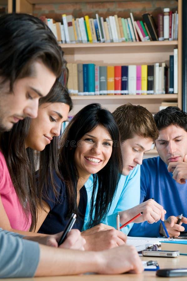 Estudiantes felices en biblioteca de universidad fotos de archivo