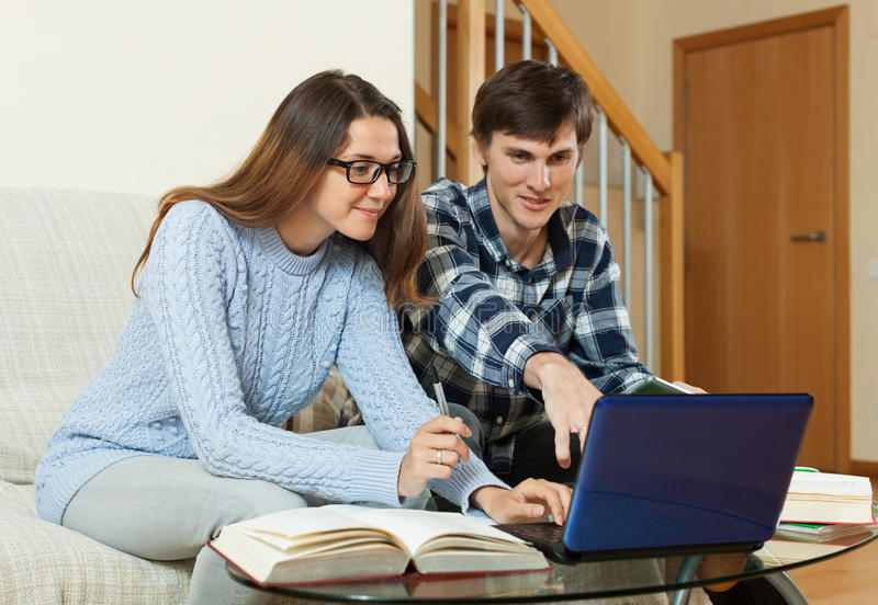 Estudiantes felices en casa que se preparan para los exámenes foto de archivo