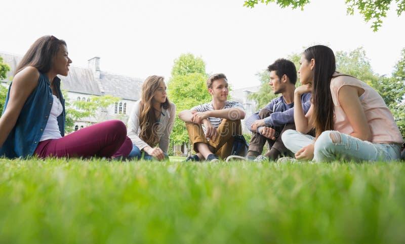 Estudiantes felices que se sientan afuera en campus imagenes de archivo