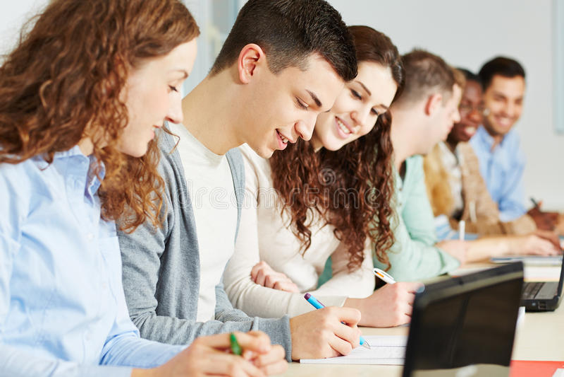 Estudiantes felices que se sientan en seminario de la universidad imagen de archivo