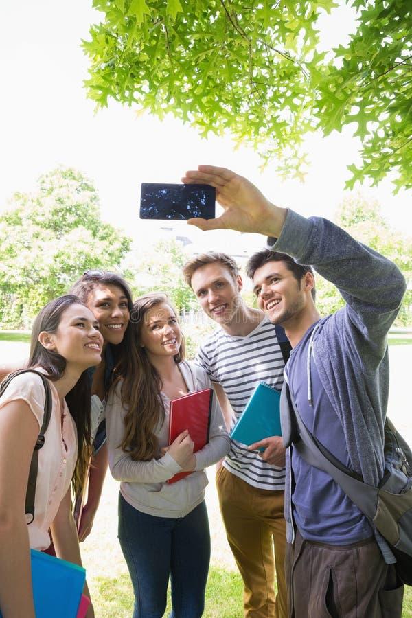 Estudiantes felices que toman un selfie afuera en campus imagenes de archivo