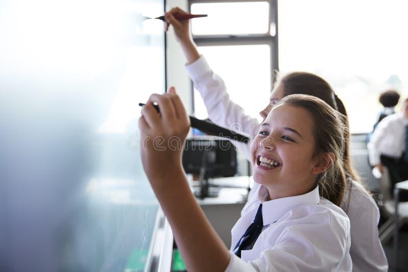 Estudiantes femeninos de la escuela secundaria que llevan el uniforme usando Whiteboard interactivo durante la lección fotografía de archivo
