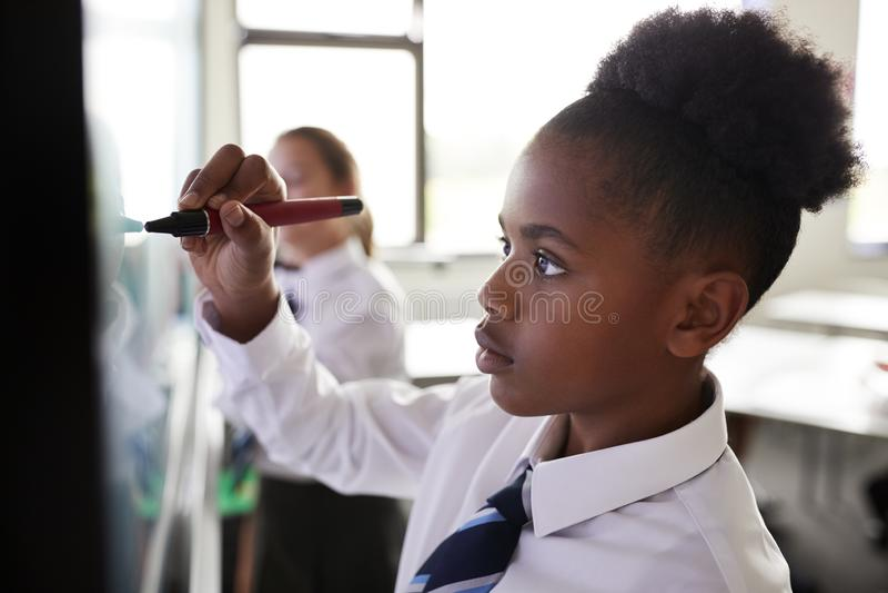 Estudiantes femeninos de la escuela secundaria que llevan el uniforme usando Whiteboard interactivo durante la lección imagenes de archivo