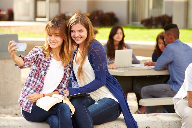 Estudiantes femeninos de la High School secundaria que toman Selfie en Campu imagenes de archivo
